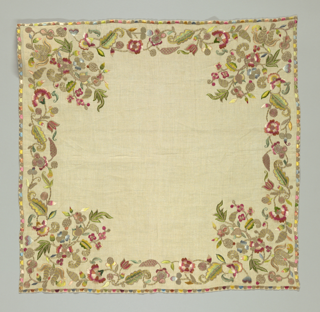 Tan square with a floral scroll in each corner, each connected by a floral vine in multi-colored thread.