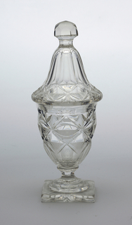 Urn-shaped, on waisted, faceted stem; thick square base; tall tapering cover with facet-cut finial; sides and cover cut with flat diamond pattern;bottom of base cut with star.