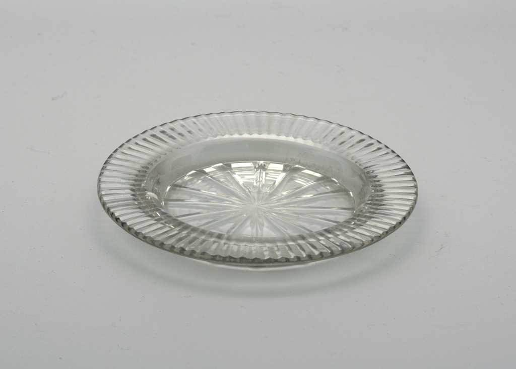 Small circular plate with flat fluted rim, star cut on center bottom.