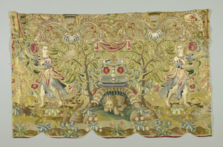 Horizontal panel of light yellow satin with multicolored silk embroidery. Design is a fountain with a lion recumbent in a grotto below it. On either side are trees with climbing Tudor roses and a man with a dog reaching toward a branch. Small flowers are scattered over the foreground. Backed with tan linen. Composed of several fragments. Fringe sewed in scallops on bottom edge.