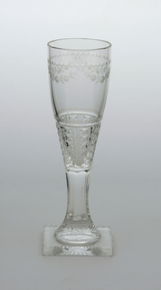 Clear glass. Square base with radiating pattern cut on bottom side; tapering stem, faceted; long narrow bowl, swelling towards top, cut and engraved with verticle bands of diamonds near base, a horizontal band of spots above, and near top edge a flower garland with a band of dots and x's above.