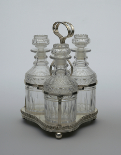 Trefoil-shaped base with applied molded rim, three ball feet; reeded frame for holding 3 decanters and stoppers, tall central circular handle.