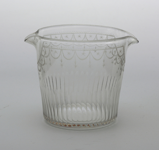 Glass with straight, slightly flared sides with two small spouts on opposite sides of rim; engraved decoration with scalloped motif at the top, alternating with hanging asterisks; lower section with vertical consecutive depressions.