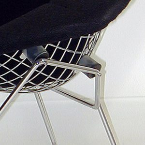 Wide, diamond-shaped form with deep seat, covered in dark gray wool; back of chair a chromed steel grid on geometric base composed of bent steel frame forming vertical and horizontal supports and runners.
