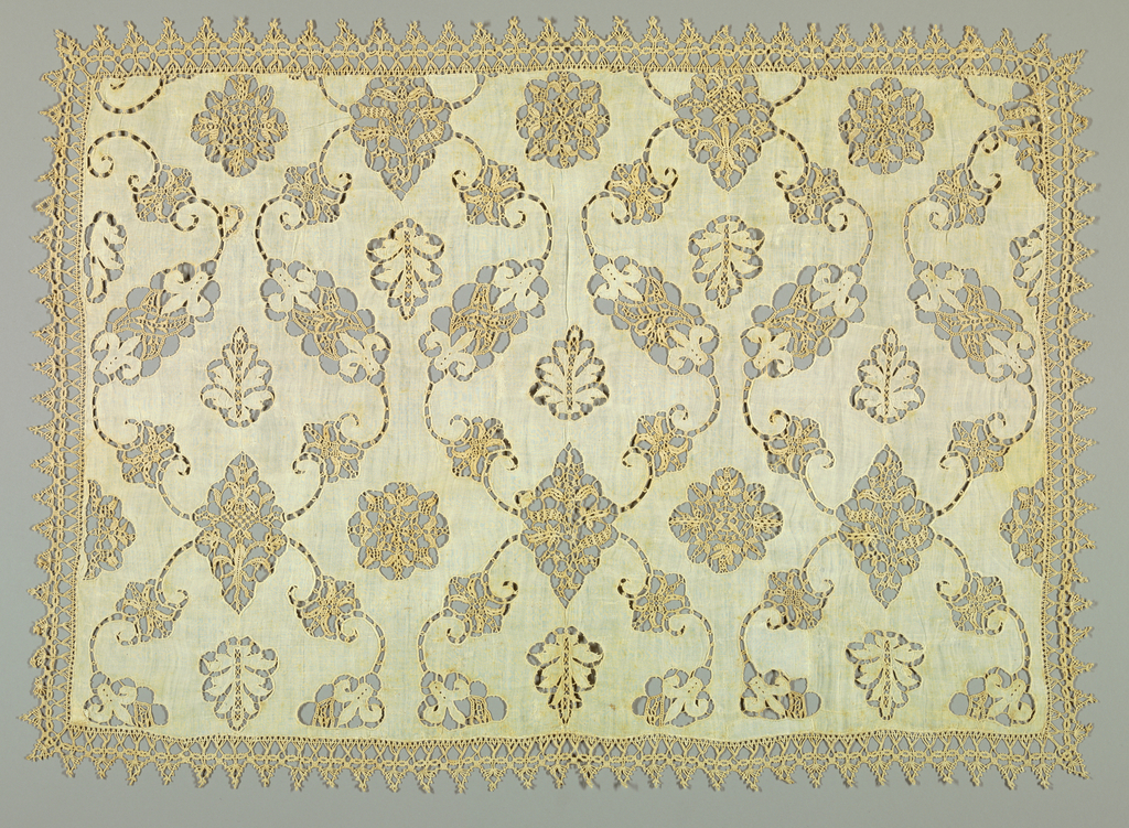 Scrolling vines and leaves cut from a foundation fabric form a repeating pattern derived from an ogee grid. Bobbin lace on all four sides.