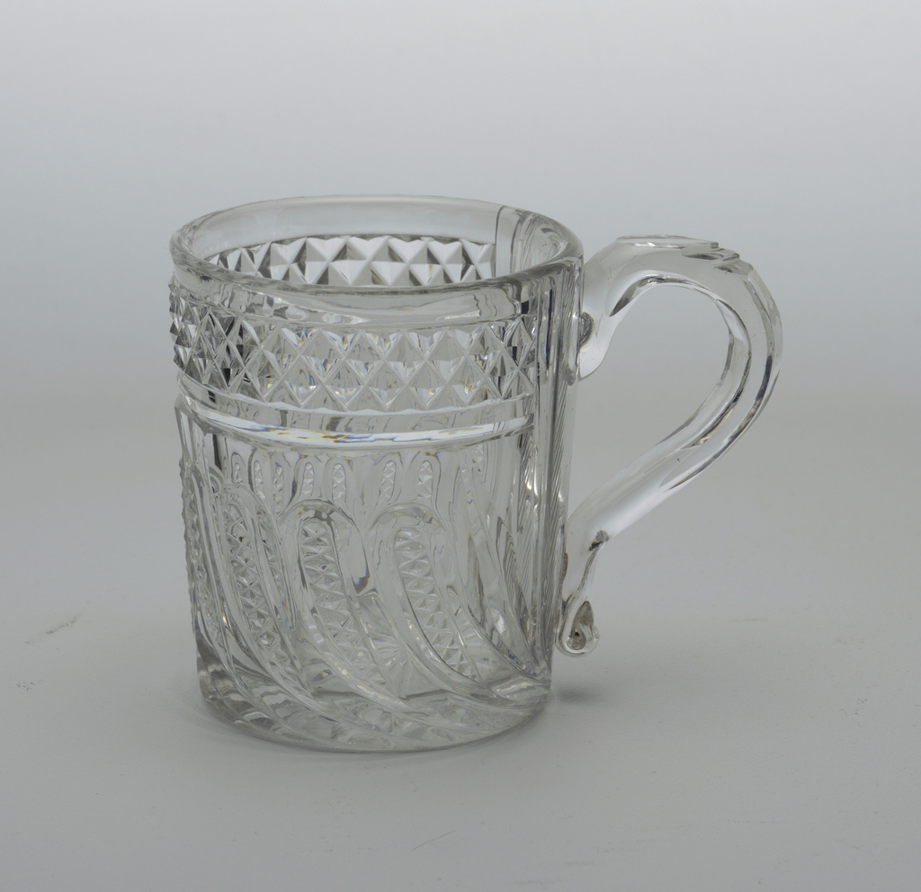 Very heavy, straight-sided body, looped and notched handle with turned up end cut with tall swirling loops of diamonds above a row of field diamonds, hatching at side near handle, on the bottom star pattern.