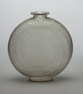 Circular form decorated with spiraling snail shell pattern; narrow neck with flaired mouth; low oval foot.