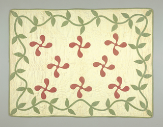 Small quilt of white cotton with applied design in red and green printed cotton, forming an all-over pattern. Piece edged by same green printed cotton; quilted in the ground.
