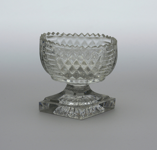 Oval-shaped bowl on spreading faceted stem on thick diamond-shaped base; cut seratted top edge, sides molded with diamond and fluting pattern, bottom of based molded star pattern