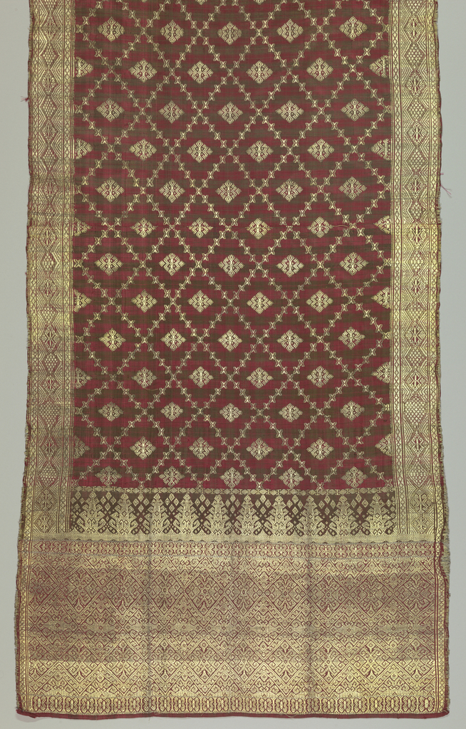 Long silk textile, probably a shoulder cloth (selendang), in dark brown against red. Plaid ground with all-over brocading of geometric pattern with center motif on main ground. Heavy brocading in borders.