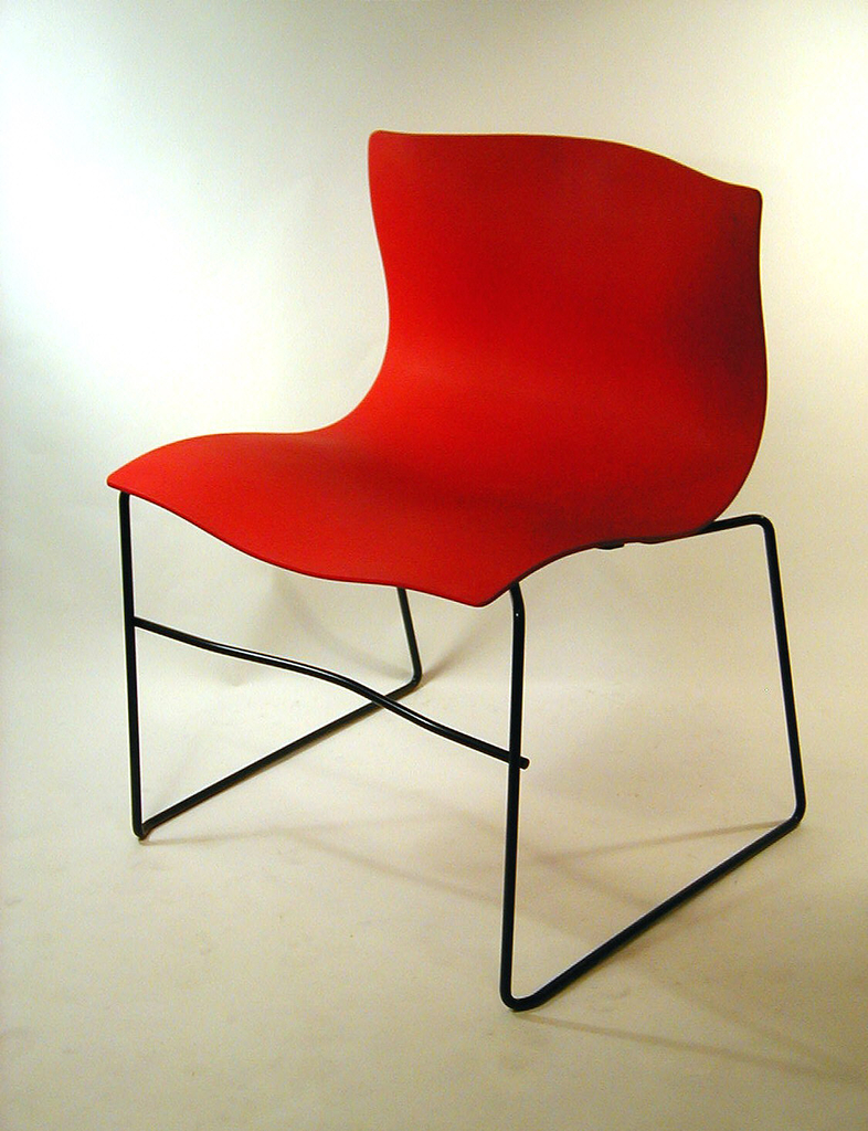 Curved back and seat made of a single red sheet with slight ripples throughout (like a handkerchief) mouned on a rectalinear black tubular metal base with a stretcher spanning the front legs.