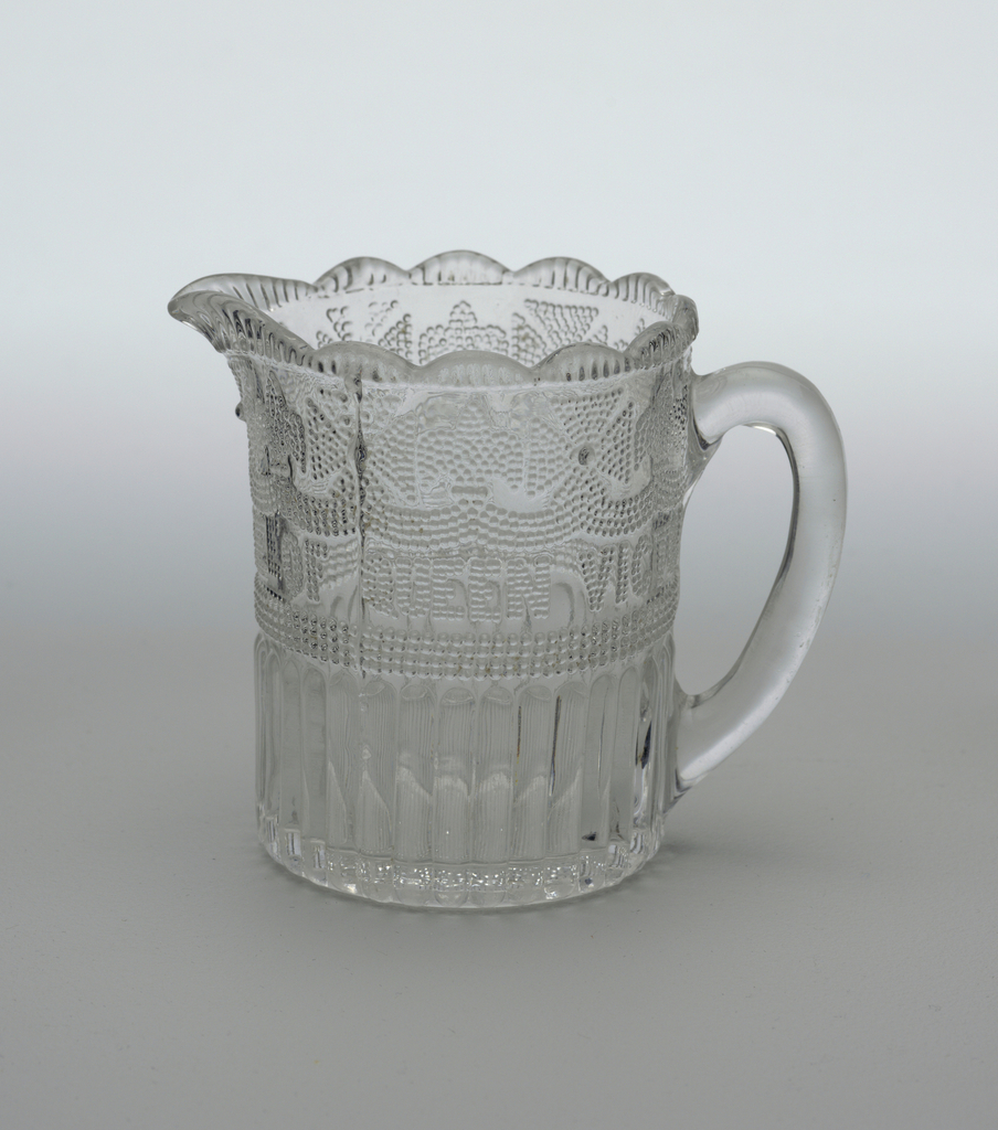 "Clear glass cylindrical form with pressed decoration. Circular scalloped mouth with spout surmounting section decorated with pressed dotted pattern of alternating Maltese cross and fleur-de-lis motifs on swags above the phrase ""JUBILEE OF QUEEN VICTORIA 1837 1887""; reeded bottom section; ovoid loop handle; crown impressed on underside of base."