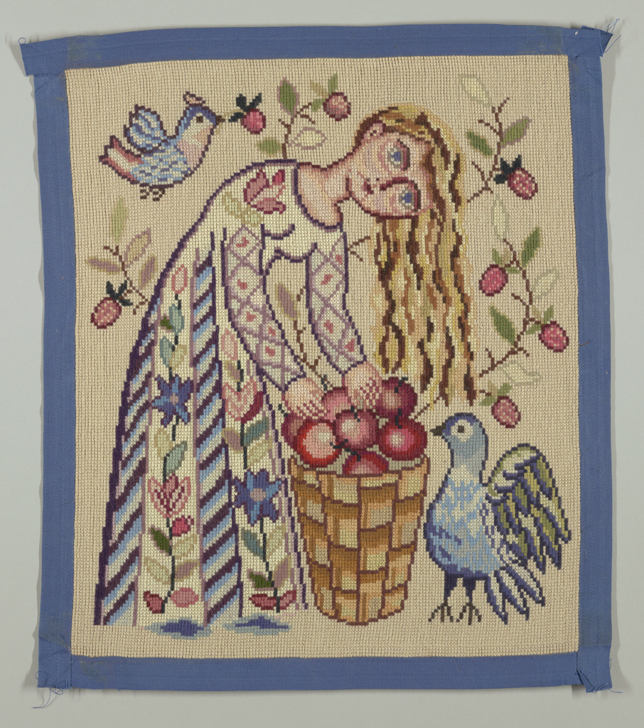 Cross-stitch needlepoint canvas depicts woman in long dress patterned  with alternating vertical rows of flowers and stepped motif, bending over basket of apples, while bird with variegated feathers stands near her, smaller bird flies overhead. Behind woman, branches of pink flowers. The forms are in shades of blue, purple, brown, peach, red, pink, and green wool on tan wool ground. Royal blue tape borders the hanging.