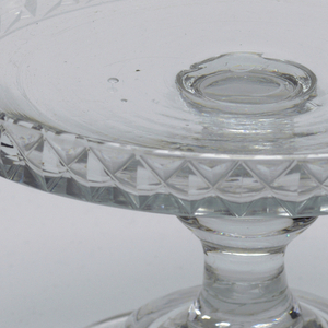 Flat circular tray with raised vertical rim cut with diamonds; tall stem with central knop; domed base with wide flat circular foot; ground pontil mark bottom.