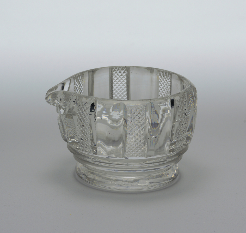 Round bowl with a pouring lip, cut with vertical pillar flutes, alternatingwith small diamonds, 2 prismatic bands below, a short round foot, ground pontil mark on bottom.