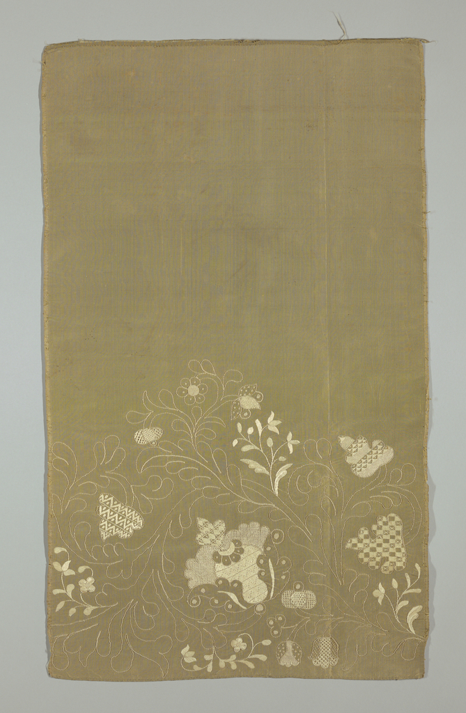 Width of silk with embroidery as a border; design of flowers and leaves in outline and in solid embroidery. Embroidery in cream on tan ground.