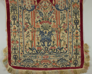 Bits of colored woolen cloth applied on a light ground in a pattern of vases containing flowers and scrolls, arranged around a niche and in borders. The niche and outer border are of red velvet; silk fringe in several colors at top and bottom.