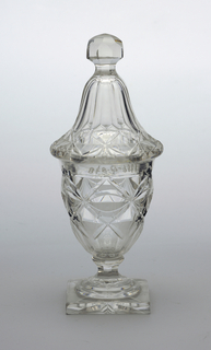 Urn-shaped, on waisted, faceted stem; thick square base; tall tapering cover with fact-cut finial; sides and cover cut with flat diamond pattern, bottom of base cut with star.