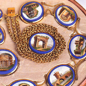 Gold necklace composed of ten ovals connected with an upper and lower gold chain. Each oval is outlined in blue with an inner image of Italian architecture. Necklace is part of a set.