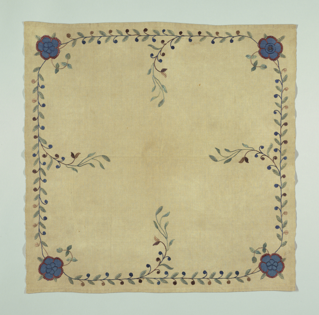 """Square table mat in undyed linen with an embroidered border. A vine with brown and blue berries appears on each side, and a blue flower is embroidered in each corner.  A signature """"D"""" is embroidered in the flower in the lower right corner."""