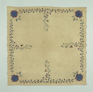 "Square table mat in undyed linen with an embroidered border. A vine with brown and blue berries appears on each side, and a blue flower is embroidered in each corner.  A signature ""D"" is embroidered in the flower in the lower right corner."