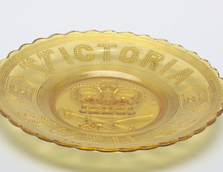 "Clear yellow circular form, the wide scalloped rim molded with the words ""VICTORIA JUBILEE"" at top and bottom, and two sheilds on left and right bearing the years ""1837"" and""1887"" respectively;  large crown above crossed sword and scepter in well."