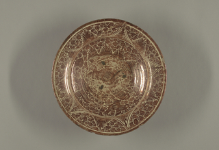 Shallow bowl with slightly flared rim; central impression at inside bottom of the bowl, not visible from reverse; circular foot ring. Decorated in copper red; small animal and two stylized birds to the left and right above, amid profusion of intricate, stylized palmette and fern motifs, set off by a circle. Five-pointed pattern, vaguely reminiscent of a star, encircles the center. Reverse decorated with concentric circles.