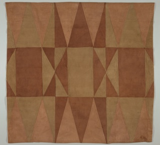 Patchwork cover of suede pieced together from triangles and rectangles in three shades of brown.