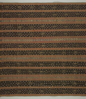 Festival sarong worn by women, of woven stripes in dark brown, coral, dark blue, and natural color. Ornamented with embroidery and pieces of mica attached in vertical rows.