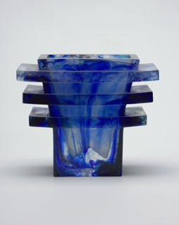 Blue transparent glass vase with stacked squares around the outside in three separate layers. The vase flares outward as do the layers.