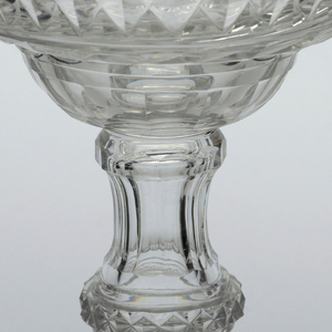 Everted double ogee bowl cut with flat flutes, blazes, a band of diamonds and a scalloped edge. Fluted stem with diamonds cut ring knop. Broad, circular domed foot has deep cut blazes in a swirl pattern. Pontil mark on bottom.