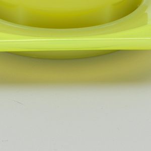 Lime green glass cup and saucer. Cup with straight sides, hexagonal base, and flat half moon handle. Hexagonal saucer and round impression for cup.