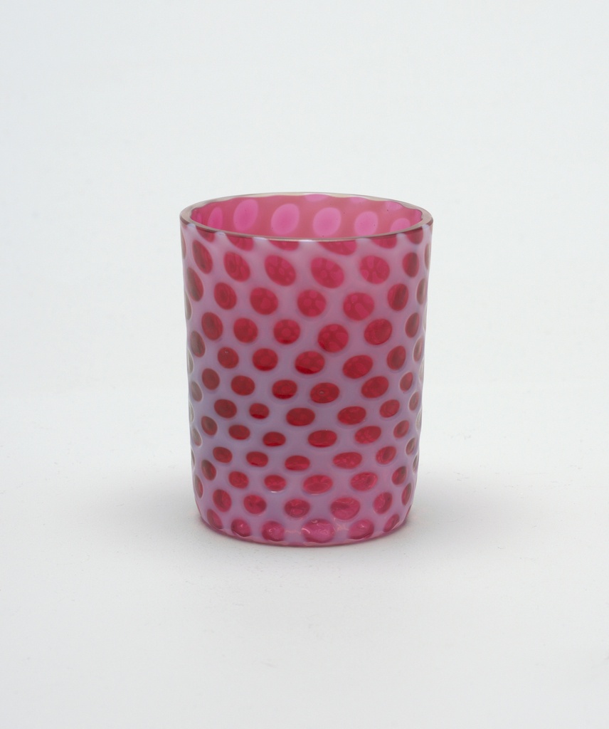 "Tapering cylindrical form cranberry-colored body with opalescent white overlay forming circular ""windows."""