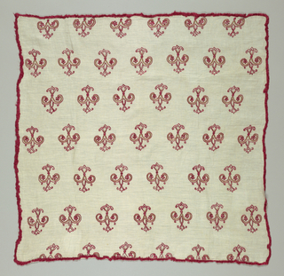 Offset rows of vertically symmetrical motifs in red and gold. Attached to the four sides is a plied cord incorporating red loops.