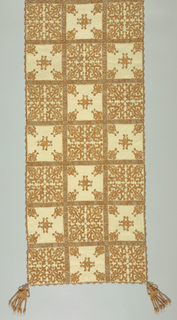 "Rectangular cover made up of small embroidered squares of two types, each a floral pattern using tan linen, 15 cm [6""] square.  Squares joined by needlework overhand knot stitch.  Edges of panel decorated with needle made bars using a large needle made and knotted tassel attached to each corner."