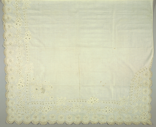 White shawl with white embroidery on three corners and two sides in floral design arranged on three borders.