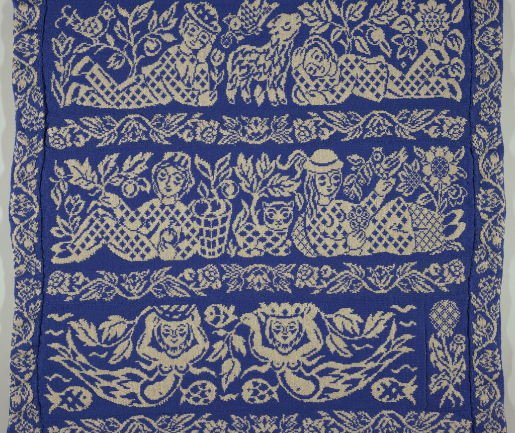"Large knitted hanging, 14 pieces sewn together, white figures on royal blue ground. Border on all 4 sides (3 ½"") scrolling floral vine. Field consists of 5 bands (11 ½"" high) of scenes alternating with narrow bands (3 ½"" high) of vines. Bottom scene: two crowned facing mermaids with flower at right, and a fish. Scene above: boy and girl adorsed with basket of apples and cat between them, surrounded by leaves. Middle scene: boy and girl facing each other with lamb and bird between them. Flowers and fruit trees surround them. Next scene: girl asleep, boy holding apple, basket of apples between them, birds flowers, and apples surround them. Top scene: two smiling facing mermaids, fish and flowers."