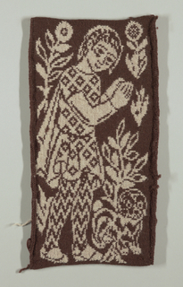 Brown and white figure of standing boy with dog and flowers on brown background. Boy is wearing tunic with pattern of diamond shapes enclosing crosses.