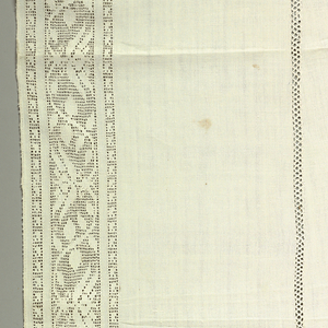 Long hanging of white linen with drawn work band on all four sides. Bobbin lace insertions in two narrow strips, and bobbin lace edging at ends. Design in drawn work is of a symmetrically curving vine with tulip-like blossoms in profile.