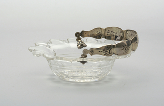 Oval bowl with wide flared lip scalloped at edge; cut with star on bottom, row of printies around base; tall silver loop handle, lobed and engraved with floral motifs, ornate mounts at joining to bowl.