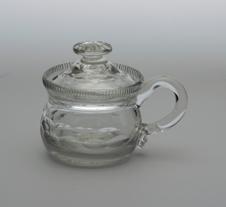 Round body with vertical fluted rim at top; loop handle; high domed lid with button finial and notch cut out for spoon; body and lid cut with double band of printies, a row of narrow flutes at base of body.