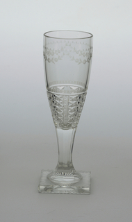 Clear glass. Square base with radiating pattern cut on bottom side; tapering stem, faceted; long narrow bowl, swelling towards top, cut and engraved with verticle bands of diamonds near base, a horizontal band of spots above, and near top edge a flower garland with a band of dots and x'sabove.