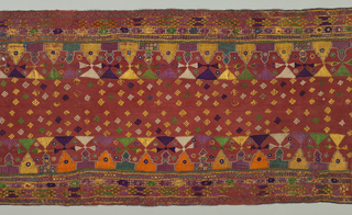 Heavy rust red cotton heavily embroidered in multi-colored silks and mirrors. Many patterned borders run parallel to the central area which is worked in small detached geometric motifs. Panel consists of two pieces stitched together.