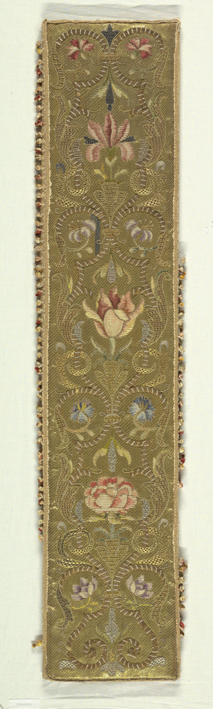 A vertical panel with a design of scrolling bands and stems with flowers and leaves worked in shades of pink, blue, lavender, green and black with gold and silver thread and and pearls on a ground on couched gold. Trimmed with ball fringe.