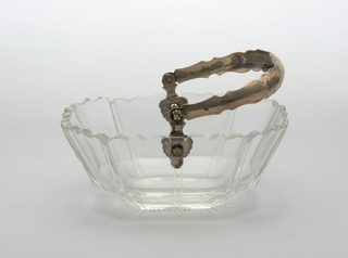 8-sided rectangular bowl, sides slightly flared, scalloped rim, sides cut with series of widely-spaced vertical lines; tall looped silver handle withshaped edges and engraved arabesques.