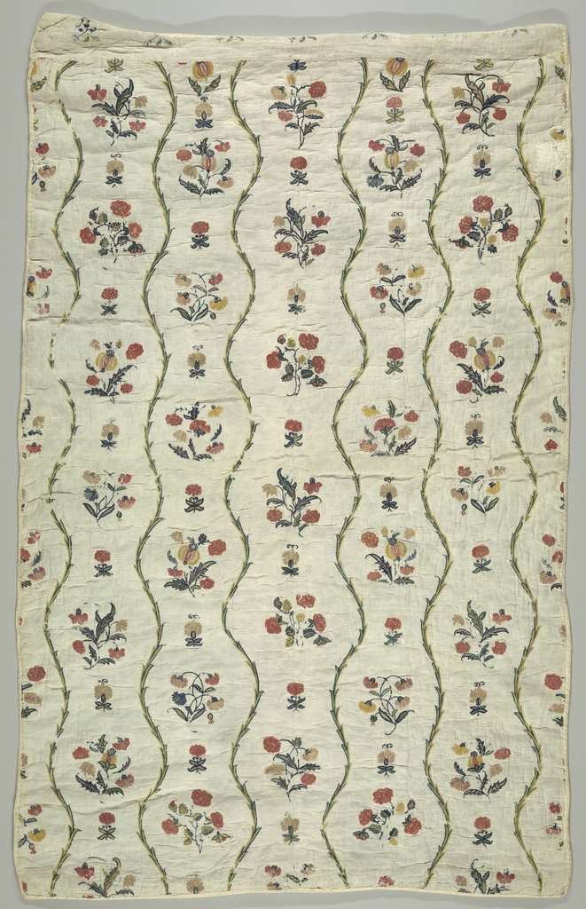 Small quilt, white linen, embroidered in polychrome wools. Design of slender undulating vine, rising vertically; detached natural size flower groups between vine stems. Background quilted, simple diagonal pattern; lined with white linen.