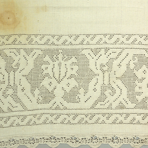 Heavy linen altar frontal with a wide border showing a large-scale design of blossoms or pomegranates within curving circular bands reserved in linen. Narrow border of simple strapwork in the same technique. Edging of heavy bobbin lace in a scalloped design.