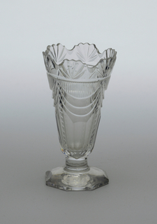 Deep fluted-shaped bowl, short tapered stem, slightly domed 8-sided foot; lip scalloped with fan cutting, below that cut drapery swags with narrow vertical flutes above and wide flutes below, foot cut with facets at edges.