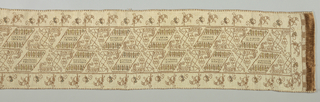 "Long rectangular cover  embroidered with a diagonal leaf and floral pattern in the field and a floral outer border using rust silk and metallic.  The field pattern incorporates ""LIBERTA""  and ""OCARAE.""  Surface satin stitch at both ends simulate fringe."