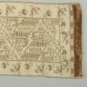 """Long rectangular cover  embroidered with a diagonal leaf and floral pattern in the field and a floral outer border using rust silk and metallic.  The field pattern incorporates """"LIBERTA""""  and """"OCARAE.""""  Surface satin stitch at both ends simulate fringe."""